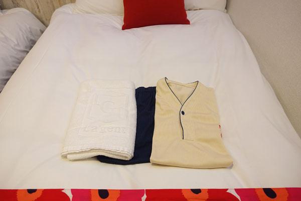 ベッドの上のバスタオルとパジャマ