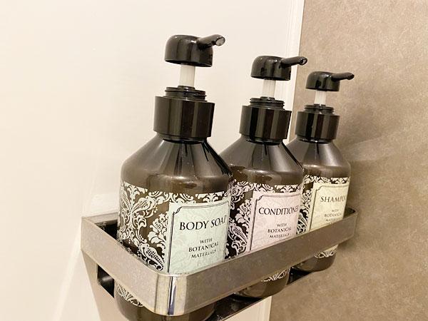シャワーブースに置かれたシャンプー、コンディショナー、ボディソープのボトル(リーガロイヤルホテル大阪)